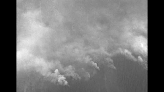 vídeos de stock e filmes b-roll de aerials of mountains and smoke from forest fires far below / pilot in an open cockpit and view through the windshield / two parachutes drop from the... - para brisas