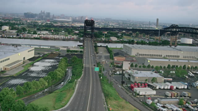 Aerials of New Jersey, Follow Lincoln Highway Bridge over Passaic River, past Warehouses & Truck Stop, with Newark in the background