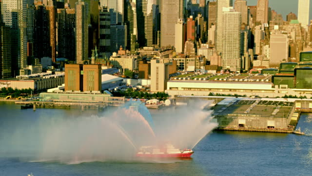 aerials of new york city, fdny fireboat spraying water on the hudson river, pull out to see midtown manhattan, at sunset. - fire department of the city of new york stock-videos und b-roll-filmmaterial