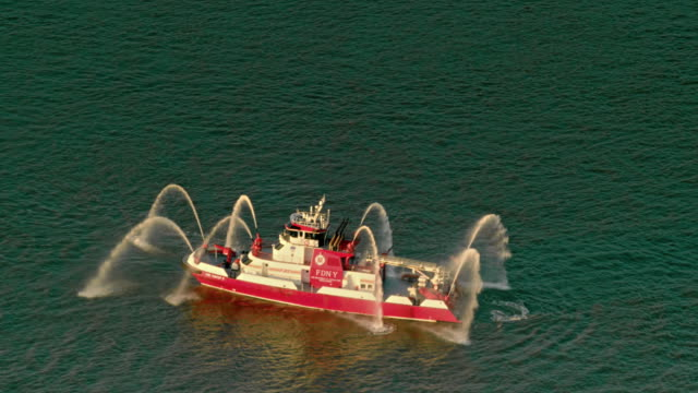 Aerials of New York City, Fire Department New York, FDNY Fireboat on the Hudson River at sunset.