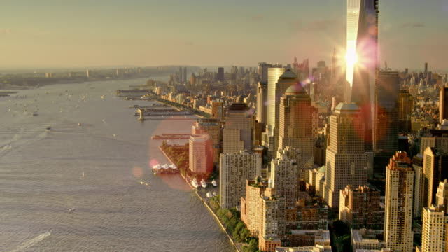 aerials of new york city, manhattan, one world trade center, freedom tower, battery park city, hudson river, sunset glints off building - one world trade center stock videos & royalty-free footage