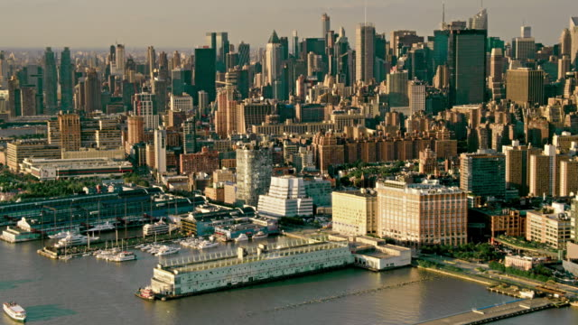 aerials of new york city, manhattan, pan from boats on the hudson river to chelsea and the iac building, with midtown manhattan in the distance, at sunset - chelsea manhattan video stock e b–roll
