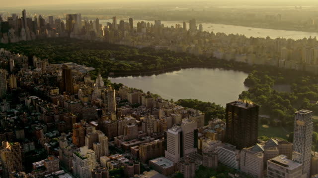 aerials of new york city, manhattan, upper east side, central park, jacqueline kennedy onassis reservoir, at sunset, with the upper west side and the hudson river in the distance. - central park reservoir stock videos and b-roll footage