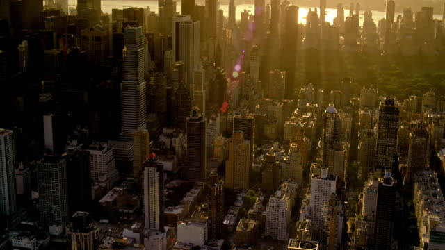 aerials of new york city, upper east side, midtown manhattan, backlit at sunset, the hudson river in the distance. - twilight stock videos & royalty-free footage