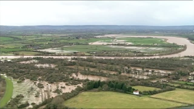 vídeos y material grabado en eventos de stock de gloucester swollen river severn surrounded by flooded fields and farmland / flooded road running through flooded fields / police car along / flooded... - río severn