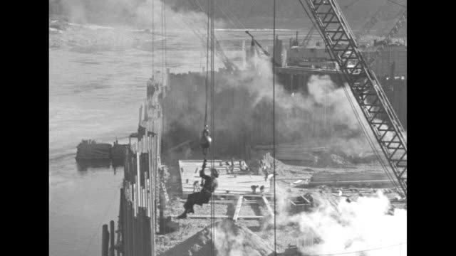 aerials on construction of grand coulee dam / man riding crane line and landing on steaming pile hammer / construction site and activity / note:... - crane construction machinery stock videos & royalty-free footage