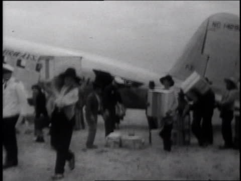 aerials over flattened city. ground shots of vips walking through. plane unloading supplies. collapsed buildings and ruins with a few people through.... - 1939 stock-videos und b-roll-filmmaterial