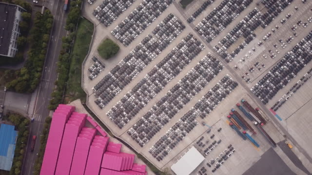 Aerials shots of vehicles sit in a depot before they are loaded onto vehicle transport ships in Shanghai China on 30 April 2018