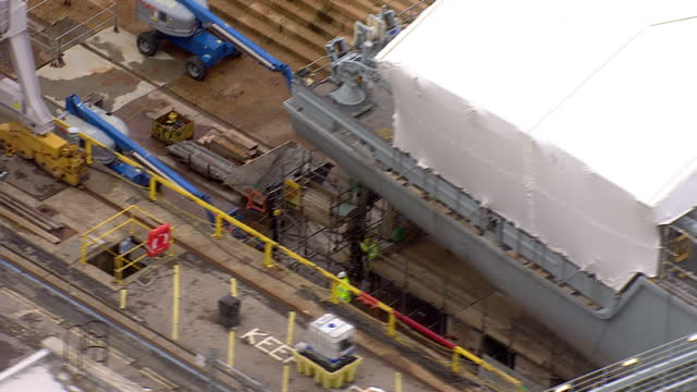 aerials shows portsmouth historic dockyard with warship under construction in dry dock on november 06, 2013 in various cities, united kingdom. - warship stock videos & royalty-free footage