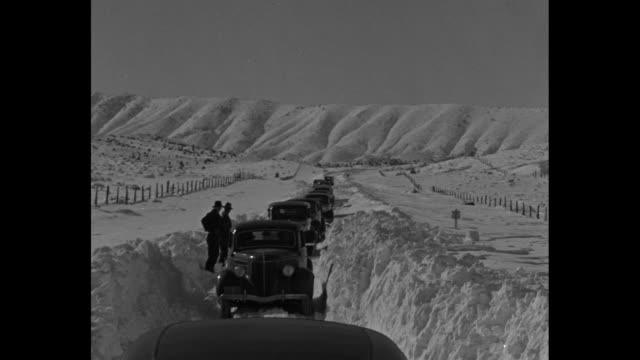aerials snow covered sierra madre mountains / line of cars drive on road in deep snow / men stand by truck stuck in snow, line of vehicles behind... - sierra madre stock-videos und b-roll-filmmaterial