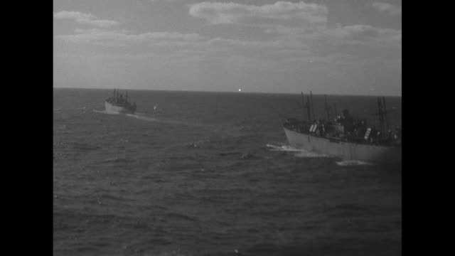 Aerials SS Cecil N Bean tows SS Henry Ward Beecher in Atlantic Ocean / VS aboard vacated Beecher life rafts stacked on deck / airplane wing as it...