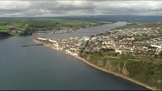 Aerials trains along Dawlish track Town of Dawlish / Coastal railway line with train out of tunnel / Train into station / Train along past rebuilt...
