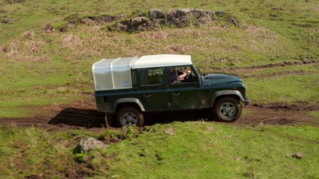 aerials truck drives through farmland - extreme terrain stock videos & royalty-free footage