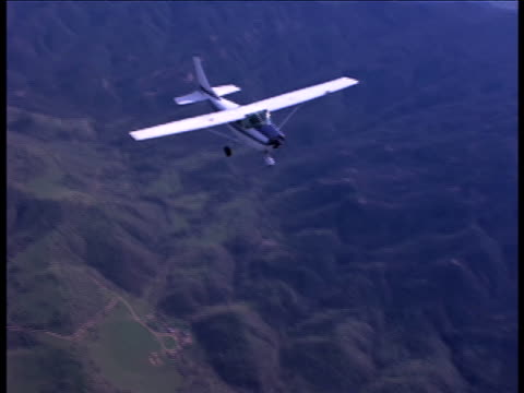 Aerial-shot of a Cessna airplane flying over a tree-covered mountain range in distress.