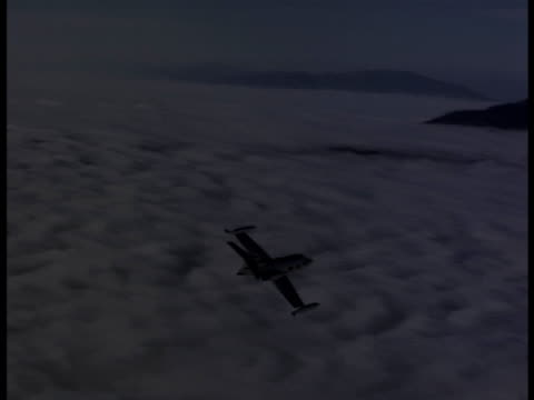 aerial-shot of a lear jet flying above the clouds and mountains. - air to air shot stock videos and b-roll footage
