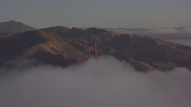 vídeos y material grabado en eventos de stock de aerial-shot over the san francisco bay and above the golden gate bridge with fog, sunlight and shadows on the hills. - pegajoso