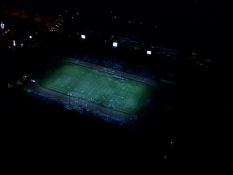 vídeos de stock e filmes b-roll de aerial-shot zooming in on lit football stadium during nighttime game. - campo de futebol