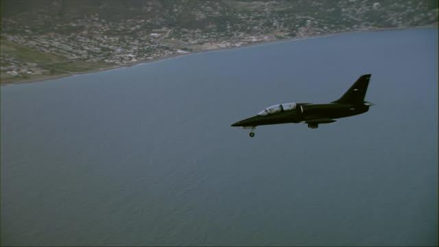 air to air, aero l-39 albatros flying over ocean towards coastline, lowering landing gear - landefahrwerk stock-videos und b-roll-filmmaterial
