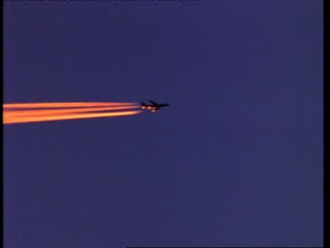 Aeroplane leaves orange vapour trails, sun glints off fuselage, England, UK