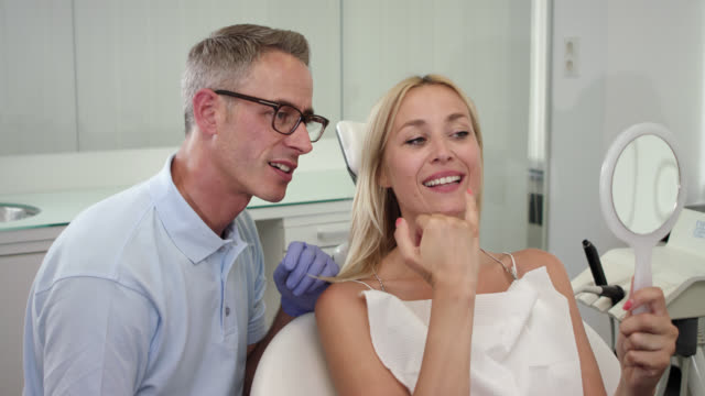 aesthetic cosmetic dentistry, dentist with greying hair in blue polo shirt and female patient with blonde hair on chair, doctor shows woman the result of the dental treatment after cleaning odontexesis and whitening the teeth, using a hand mirror. - polo shirt stock videos & royalty-free footage