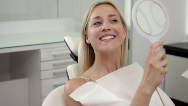 aesthetic cosmetic dentistry, female patient with blonde hair on doctor's office chair, woman with hand mirror checking the result of the dental treatment after cleaning odontexesis and whitening the teeth. - teeth whitening stock videos and b-roll footage