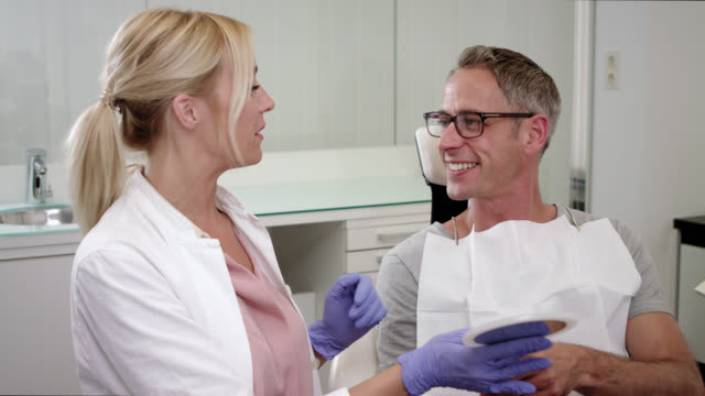 aesthetic dentistry dentist's office, male patient sits on chair after receiving dental care check up, teeth whitening bleaching and professional tooth cleaning, female doctor with long blonde hair wearing exam gloves shows man the result using a mirror - teeth whitening stock videos and b-roll footage