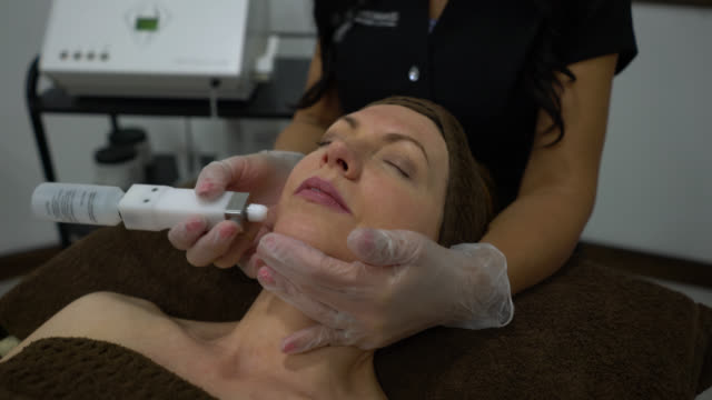 vídeos de stock, filmes e b-roll de aesthetician que faz um eletroterapia facial ao cliente fêmea - spa treatment