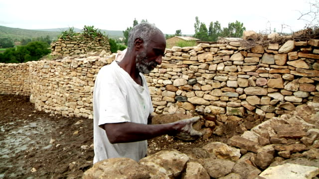 afar men building stone enclosure on august 16 2011 on road from makele to addis ababa ethiopia - enclosure stock videos & royalty-free footage
