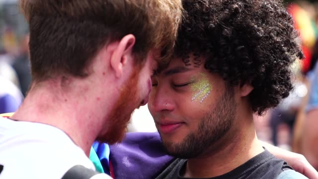affection moment of gay couple in gay pride parade - gruppo multietnico video stock e b–roll