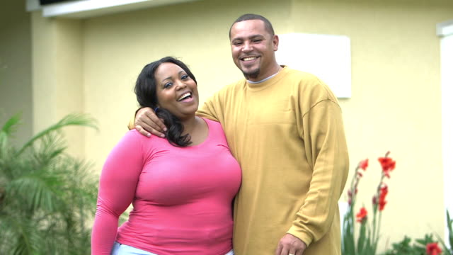 Affectionate black couple standing outside home
