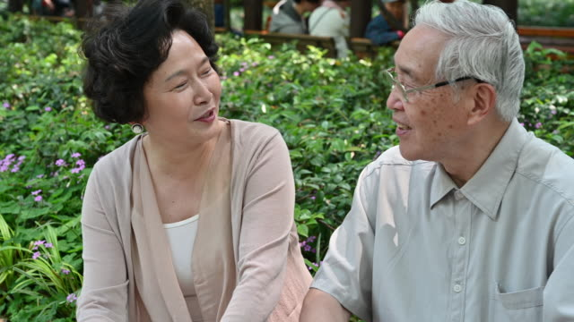 affectionate chinese senior couple chatting in the park - sideways glance stock videos & royalty-free footage