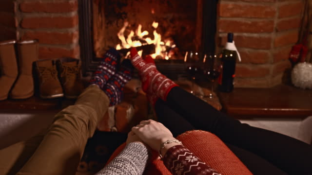 affectionate couple by the fireplace - sock stock videos & royalty-free footage