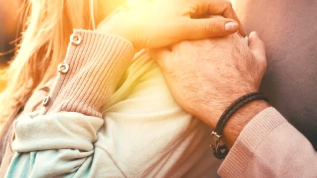 vídeos de stock e filmes b-roll de affectionate couple holding hands - retroiluminado