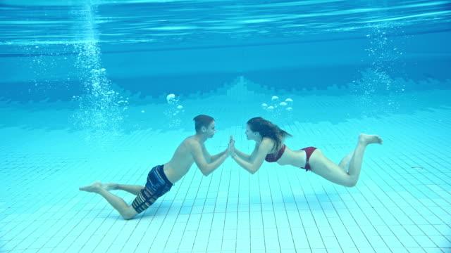 vídeos de stock e filmes b-roll de slo mo affectionate couple in the swimming pool - 20 24 anos