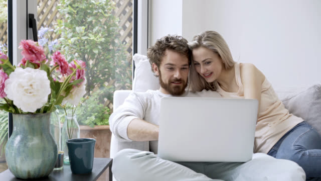 affectionate couple looking at photos on their laptop - face to face stock videos & royalty-free footage