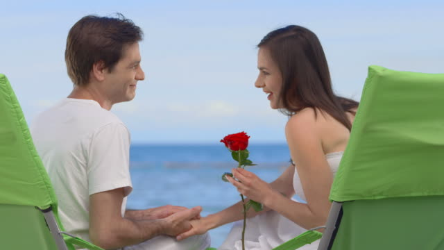 vídeos de stock, filmes e b-roll de hd: carinhoso casal na praia - cadeira dobrável