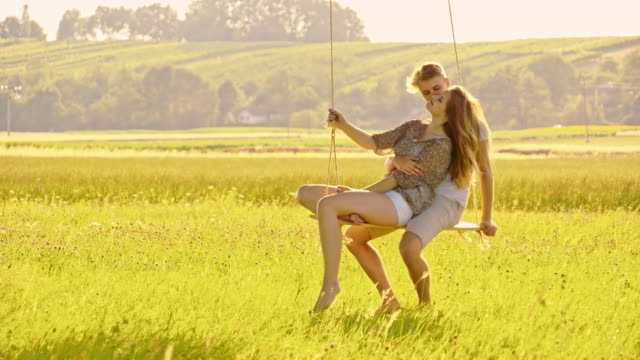 slo mo  affectionate couple swinging on a tree swing - rope swing stock videos & royalty-free footage