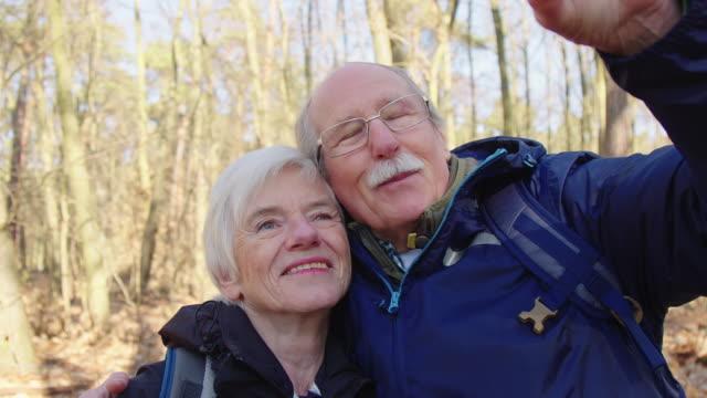 愛情深いカップルは、ハイキング中に自分撮りを取る - 自分撮り点の映像素材/bロール