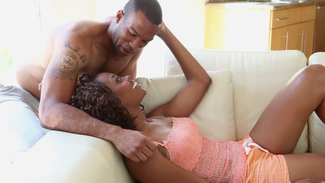 vídeos y material grabado en eventos de stock de affectionate couple talking and relaxing on sofa - camisola