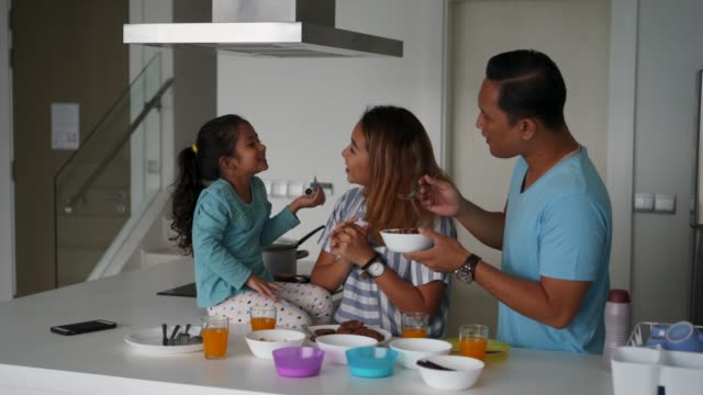 affectionate family preparing breakfast at home - cultura malesiana video stock e b–roll