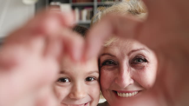 Affectionate grandmother and granddaughter making heart gesture looking at camera