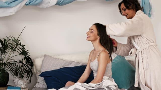慈母の娘の髪をとかす - 髪をブラシでとく点の映像素材/bロール