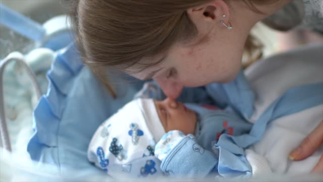 affectionate mother with her newborn - occurrence stock videos & royalty-free footage