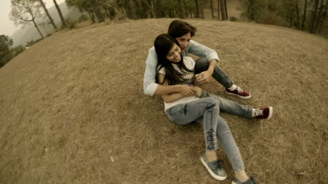 Affectionate multiethnic young couple romancing together in hills.