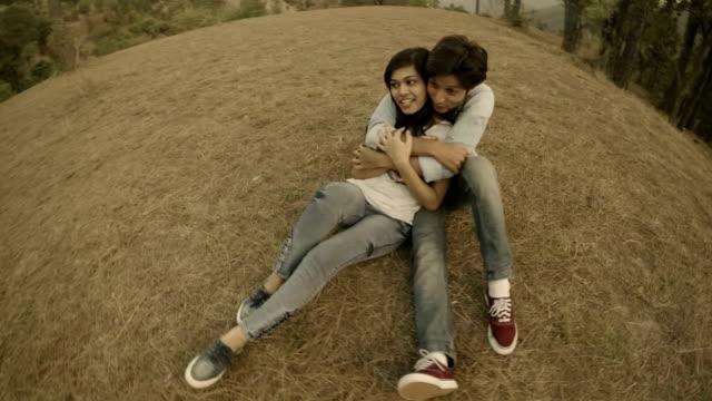 Tillgiven multietniskt ungt par romancing tillsammans i hills.