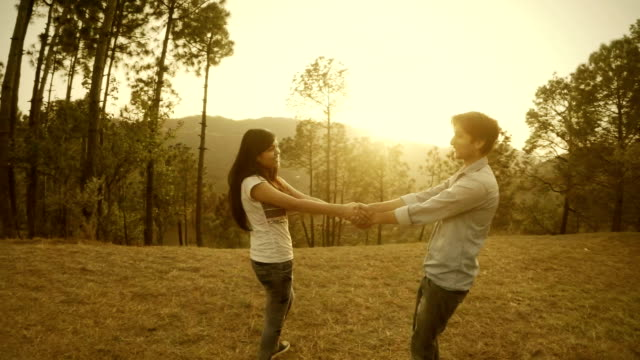 Affectionate multiethnic young couple spinning together in hills.