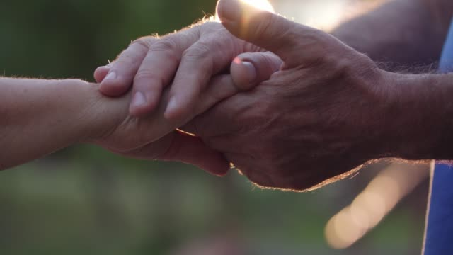 affectionate senior couple holding hands during sunset - human hand stock videos & royalty-free footage