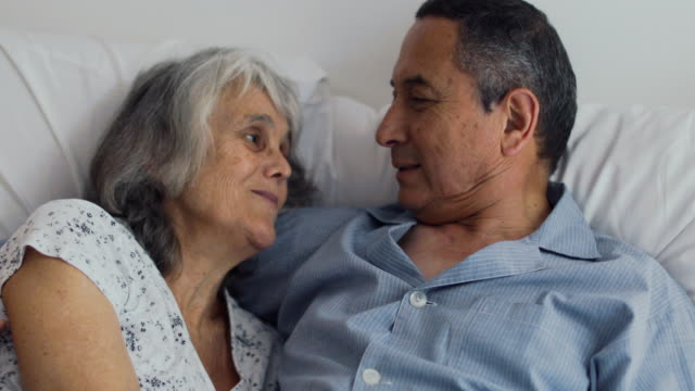 affectionate senior latin couple in the bed in early morning - assertiveness stock videos & royalty-free footage