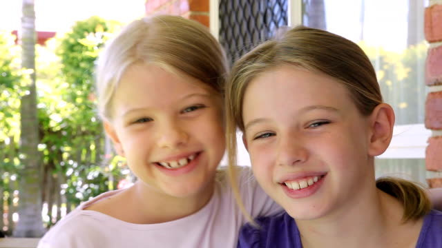 affectionate sisters little girls giving a hug - giving stock videos and b-roll footage