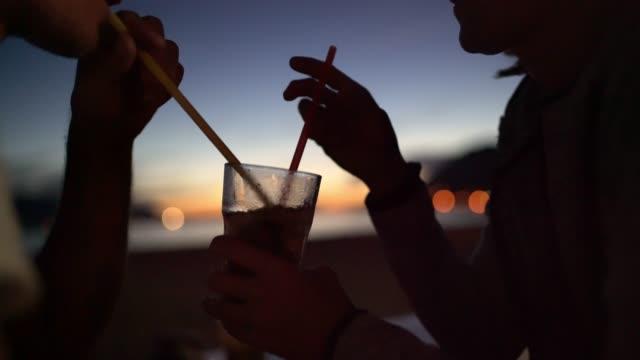 cu liebevolle touristen-paar teilen in der abenddämmerung cocktail mit einem strohhalm auf terrasse - real wife sharing stock-videos und b-roll-filmmaterial